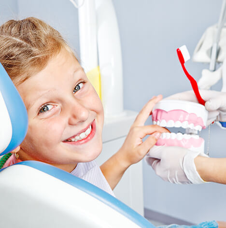 boy smiling as a dentist shows him a plastic model of a set of teeth
