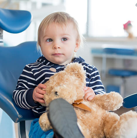 young boy sitting in a dental chair with his teddy bear