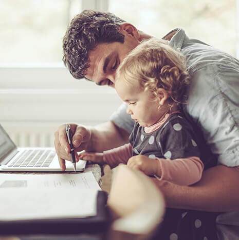 father playing with his infant daughter in front of a laptop computer