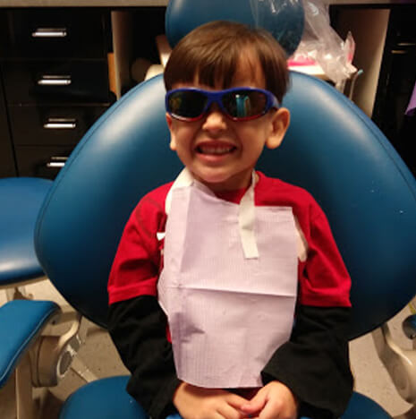 young boy wearing sunglasses and smiling while sitting in a dental chair