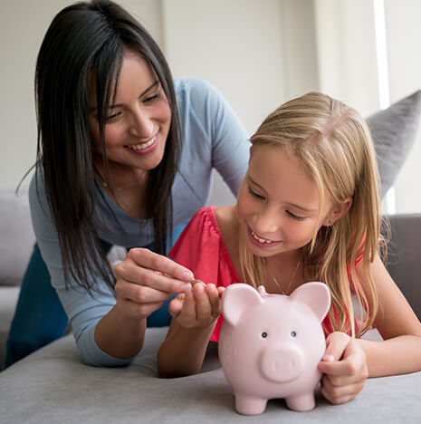 mother helping her daughter put money in a piggy bank