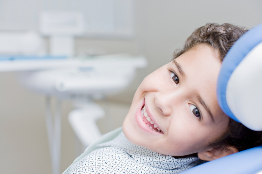 Brunette boy smiles while sitting in the dental chair at his pediatric dentist in San Antonio, TX