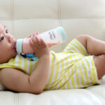 Baby relaxes on the couch as he drinks from a bottle