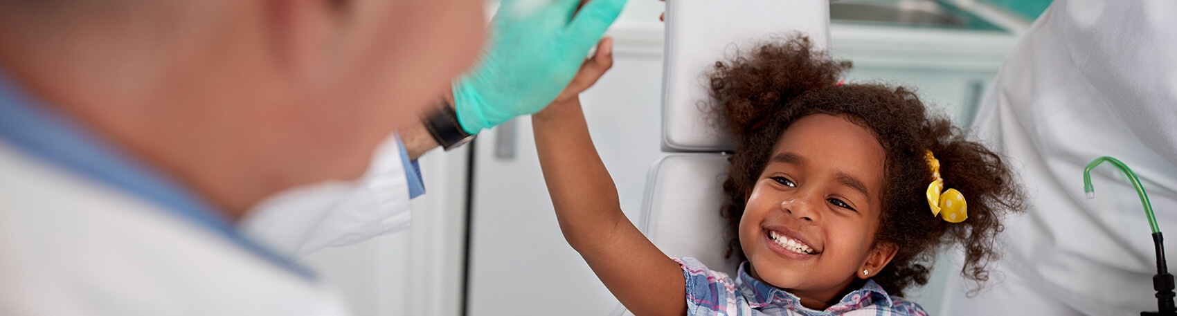 young girl giving her dentist a high five